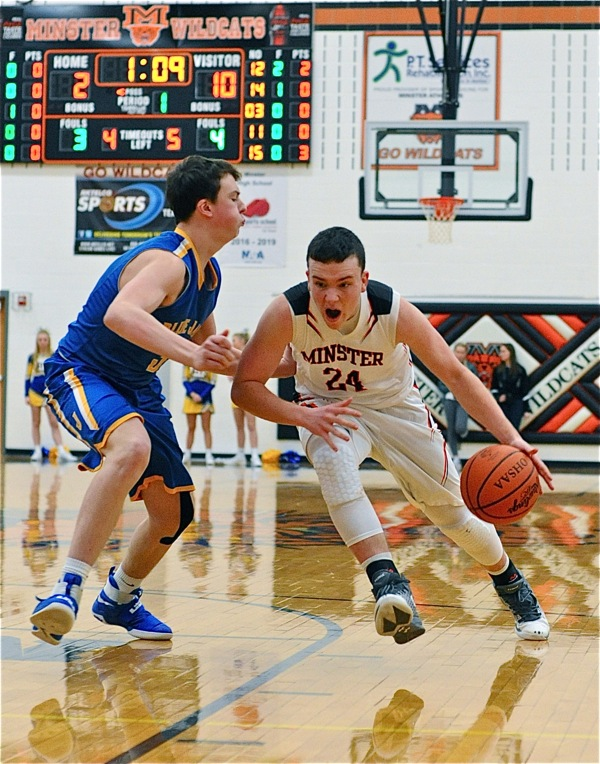 Minster's Aaron Ernst drives past a St. John defender.