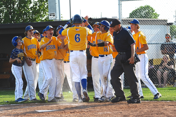 Russia's Hunter Lohee is mobbed by teammates after his solo home run in the sixth inning.