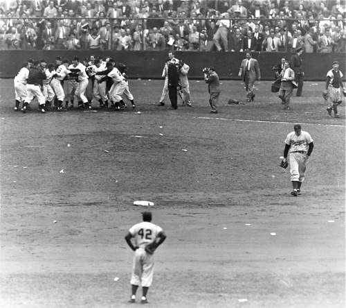 An iconic New York press photo from the climax of the Giants-Dodgers playoff game in October, 1951.  Dodger second baseman Jackie Robinson (#42) watches the Giants celebrate Bobby Thomson's home run while pitcher Ralph Branca walks away in dejection.