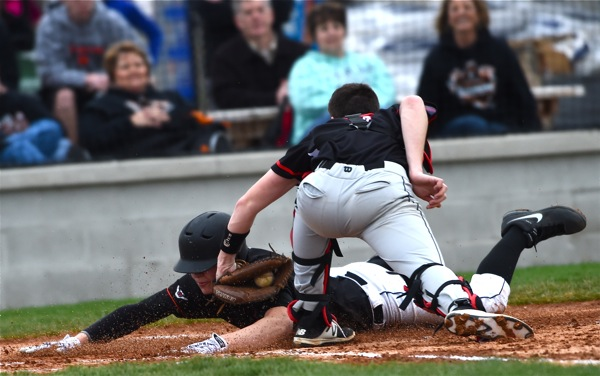 Pitcher Noah Richard slides head first past the tag attempt of Covington's Mason Dilley for the game's first run.