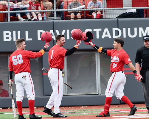 Tyler Cowles is greeted by Brady Cherry and Bo Coolen after his fourth inning homer in game one.