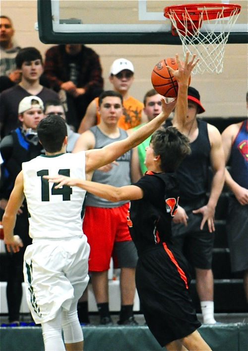 Asked to play harder on defense by their coach, Coldwater's Jacob Wenning slaps away the shot attempt of Greenville's Kyle Mills.