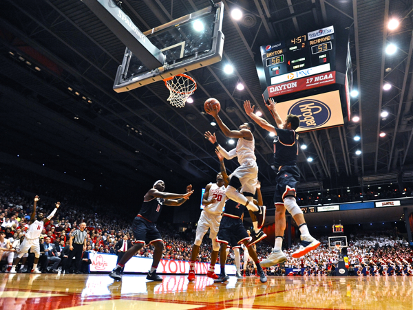 """Scoochie Smith signals """"field goal"""" (background) as Charles Cooke beats the Richmond defense to the rim."""