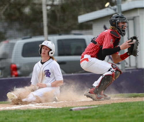 Recovery's Cade Wendel slides past St. Henry catcher Connor Bruggeman for a first inning run.