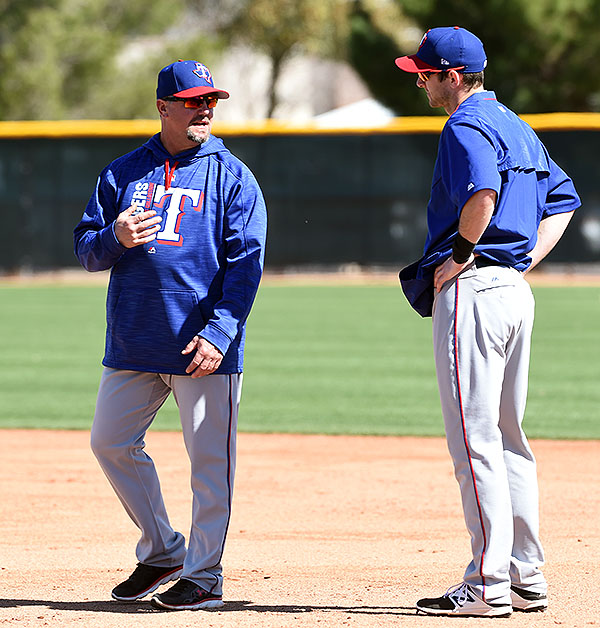 Hoying (right) gets some base-running tips from a coach during morning drills in the Rangers' camp.
