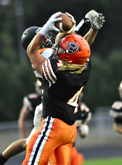Coldwater's Kraig Schoenherr outduels a Minster defender for catch in the Cavaliers' 28-0 win.