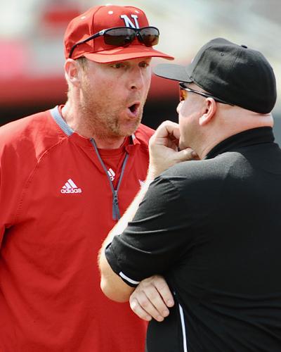 Troy's Deron Brown, who's umpiring this weekend series, gets an earful from Nebraska head coach Darin Erstad.
