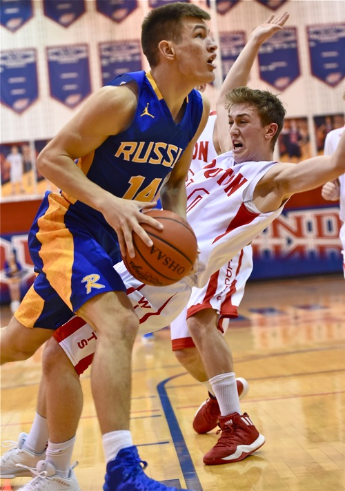Russia's Drew Poling plows through Houston's Howie Ludwig on his way to the rim in Wednesday's win.