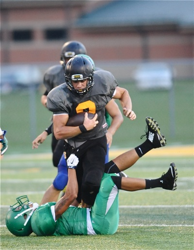 'Jackets' running back Isaiah Bowser runs through a would-be tackler on his way to first down in Thursday's scrimmage.