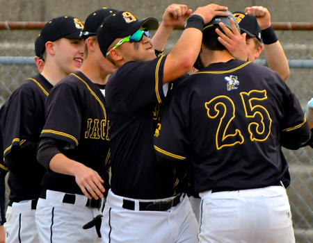 Cole Hoffman #25 and his teammates celebrate after he hits a homerun.