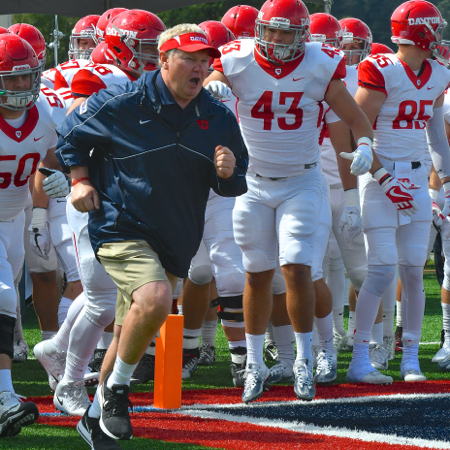 UD Head Coach, Rick Chamberlin leads his Flyers on the field for their first game of the season.