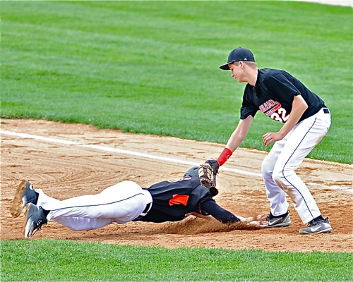 Fort Loramie first baseman Jerrod Middendorf tags out Versailles' Noah Richard attempting to get back to first base.